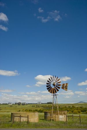 Lonely windpump landscape with blue skies and some white clouds Stock Photo