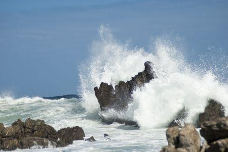 Waves crashing violently on big rocks making huge splashes, with blue skies baove and behind Stock Photo