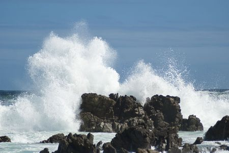 Waves crashing violently on big rocks making huge splashes, with blue skies baove and behind Stock Photo