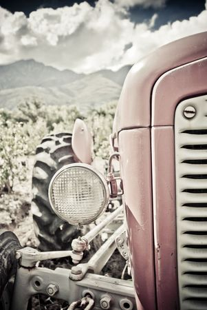 Old red tractor with clouds and vineyards in the background Stock Photo