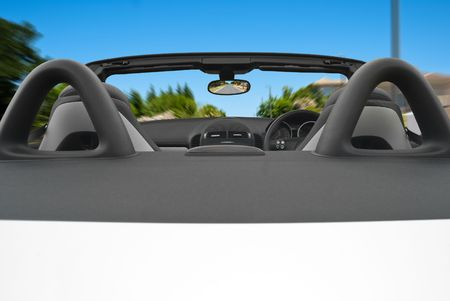 Interior of a speeding convertible car with clear blue skies overhead