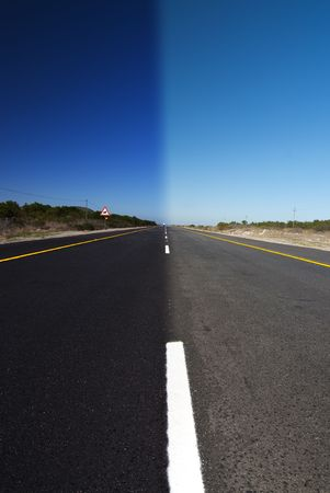 An road with clear blue sky above. One half is in full daylight, and the other half in darkness Stock Photo