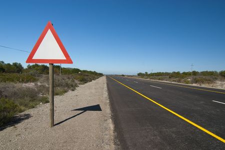 Red and white triangular road-sign next to road with clear blue skies above photo