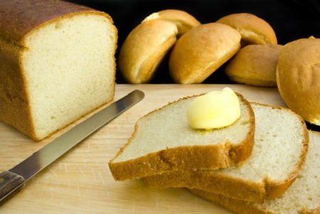 Slices of bread and buns and some butter, isolated on a black background Stock Photo