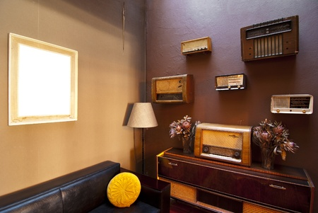 Vintage room with antique radios against the brown walls. There is a frame with white for compositing photo
