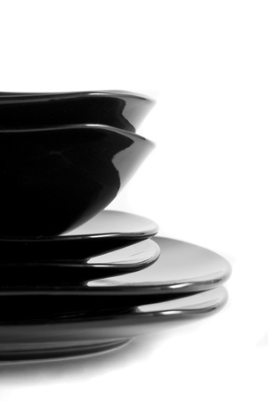 Black plates and bowls stacked on top of each other on a white background Imagens