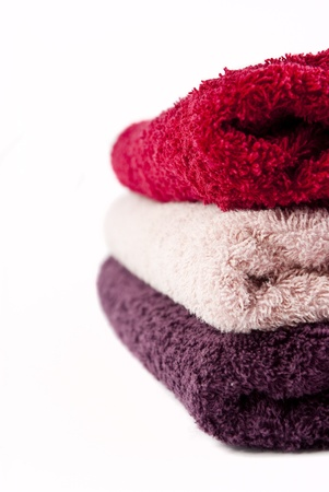 Pink, red and purple towels stacked on top of each other on a white background photo