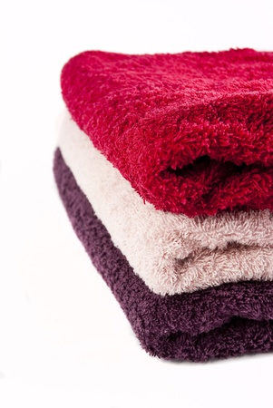 Pink, red and purple towels stacked on top of each other on a white background