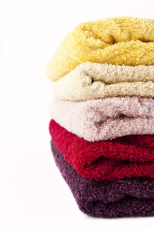 Pink, yellow, red and purple towels stacked on top of each other on a white background photo