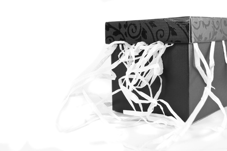 Black gift box with details on the top, and white tinsel hanging out, isolated on a white background