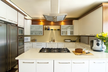 Modern kitchen with white and wood finished, and a silver hob overhead Stock Photo - 10715271