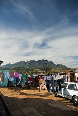 Various clothing lines with clothes hanging out to dry in front of shacks in a township in South Africa, with the mountains in the background