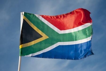 South African flag flying in the wind with blue skies and clouds in the background Stock Photo