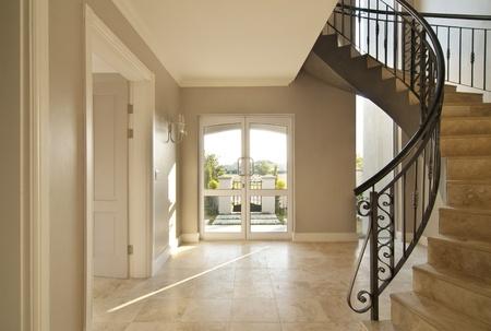 schody: Schody i drzwi z przodu obszar nowoczesnego domu. Klatka schodowa jest w ramce po prawej stronie i na zewnątrz jest widoczne przez drzwi. Zarówno schody i podłoga wyłożone Zdjęcie Seryjne