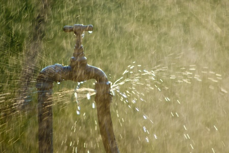 llave de agua: Grifo oxidado con el rociado de agua de ella. Más gotas cayendo en todo el bastidor, con un fondo verde