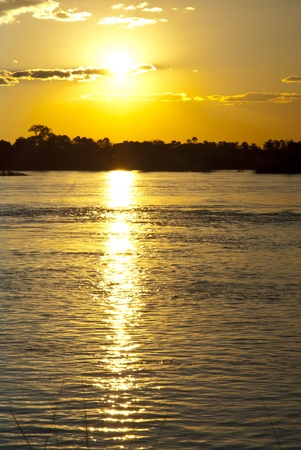 Sun setting over the Zambezi river with clouds in the sky, with the river in the foreground photo