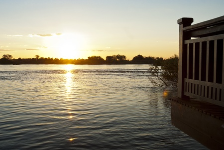 Sun setting over the Zambezi river with clouds in the sky, with a wooden porch overhanging onto the water in the foreground photo