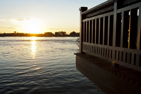 zambezi: Sun setting over the Zambezi river with clouds in the sky, with a wooden porch overhanging onto the water in the foreground Stock Photo