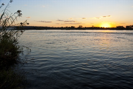 zambezi: Sun setting over the Zambezi river with clouds in the sky, with the river in the foreground