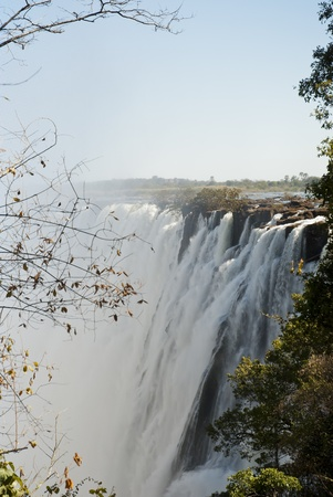 zambezi: Victoria waterfall with some vegetation in the foreground and blue skies overhead Stock Photo