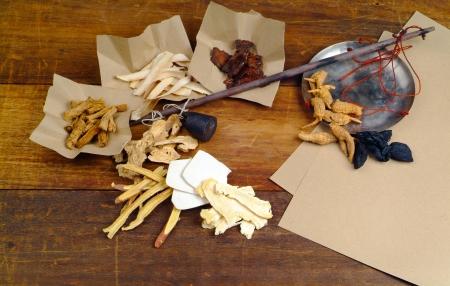 medicina tradicional china: Las hierbas medicinales chinas en el fondo de madera Foto de archivo