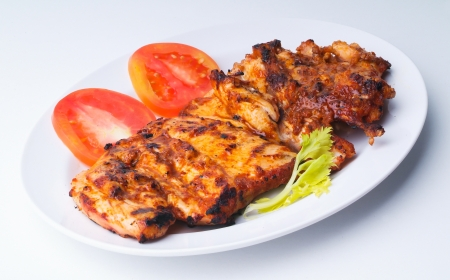 Grilled chicken on a white plate with vegetables on the background. photo