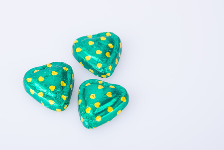 Chocolate or green foil heart-shaped chocolate on a background Stock Photo