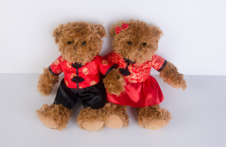 toy or teddy bear with chinese red shirt on background