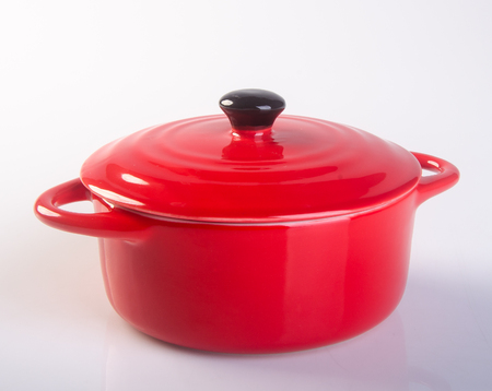 olla o una olla con tapa roja en el fondo