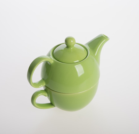 Porcelain tea pot and cup on grey background