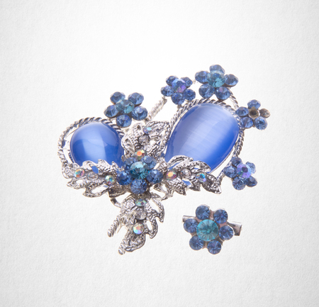 brooch or brooch with different gems on a background