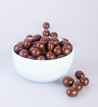 Chocolate balls in a white bowl on white background.