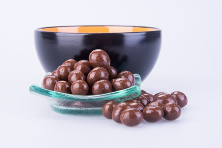 Chocolate balls in a plate besides a bowl on white background
