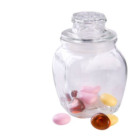 Candies or colorful candies in glass jar on background