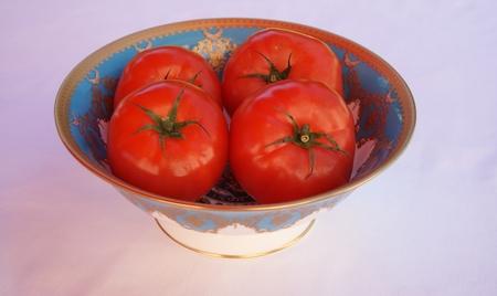 Crisp red beef tomatoes on a porcelain porcelain bowl