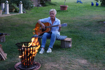 The flames of the campfire are reflected in the guitar Stock Photo