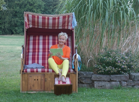 Even in a roofed wicker beach chair, the attractive woman with the tablet is always up to date Stock fotó