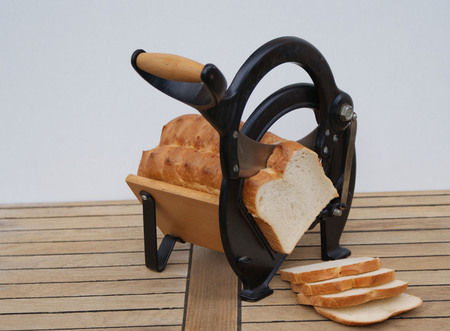 Old Danish bread slicer on wooden background with white bread slices