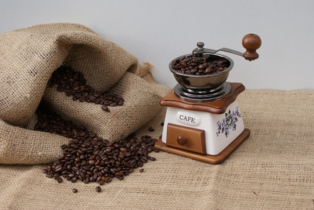 Old coffee grinder with filled coffee beans next to a coffee sack 版權商用圖片