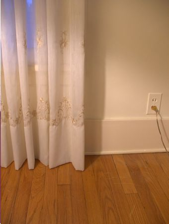 cream colored: A home interior with cream colored curtains & hardwood floors.