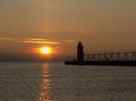 lake michigan lighthouse: El faro en el embarcadero del sur del asilo en el lago Michigan apenas como el sol est� fijando.