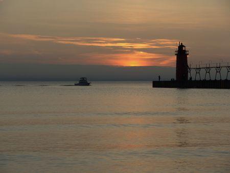 lake michigan lighthouse: El sol acaba de establecer en el Lago Michigan como un barco se aproxima a la South Haven, Michigan faro.