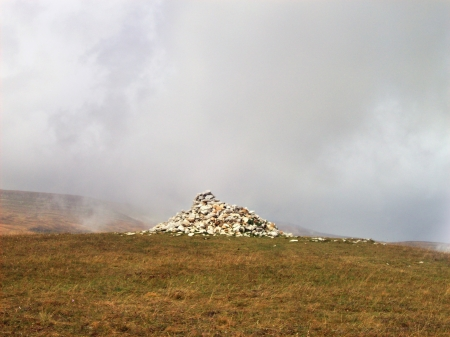 Plateau with withered grass with a cairn and fog covering the background  Stock Photo