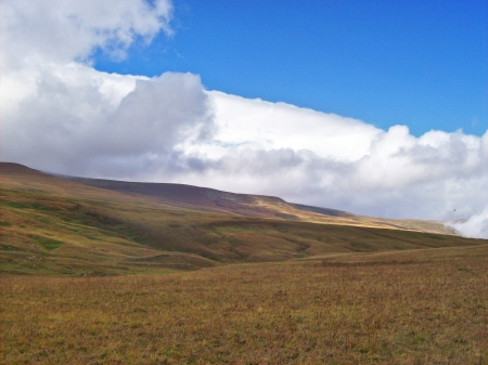 Plateau with withered grass on a background of  blue sky with white clouds
