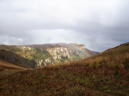 Mountain landscape with clouds and sunlit places and a rainbow after the rain