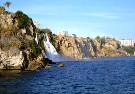 Steep shore with a waterfall on a background  the sky.