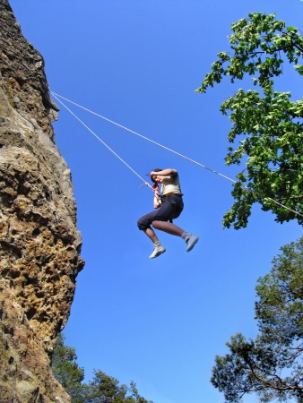 belay: Novice climber trains down the cliff using belay ropes.