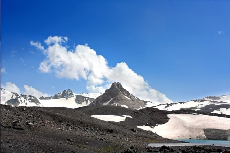 Black mountain with snow and glades conical apex at the center on a background of blue sky with clouds. Elbrus.