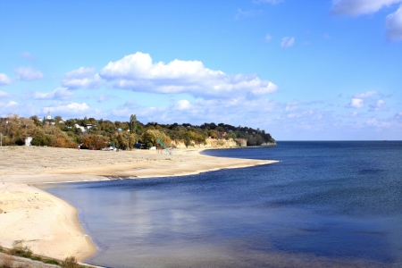 Sea, sandy beach and a residential village in the background on a clear day. Stock Photo