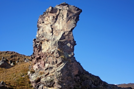 Large stone pillar of naked rock against the blue sky.